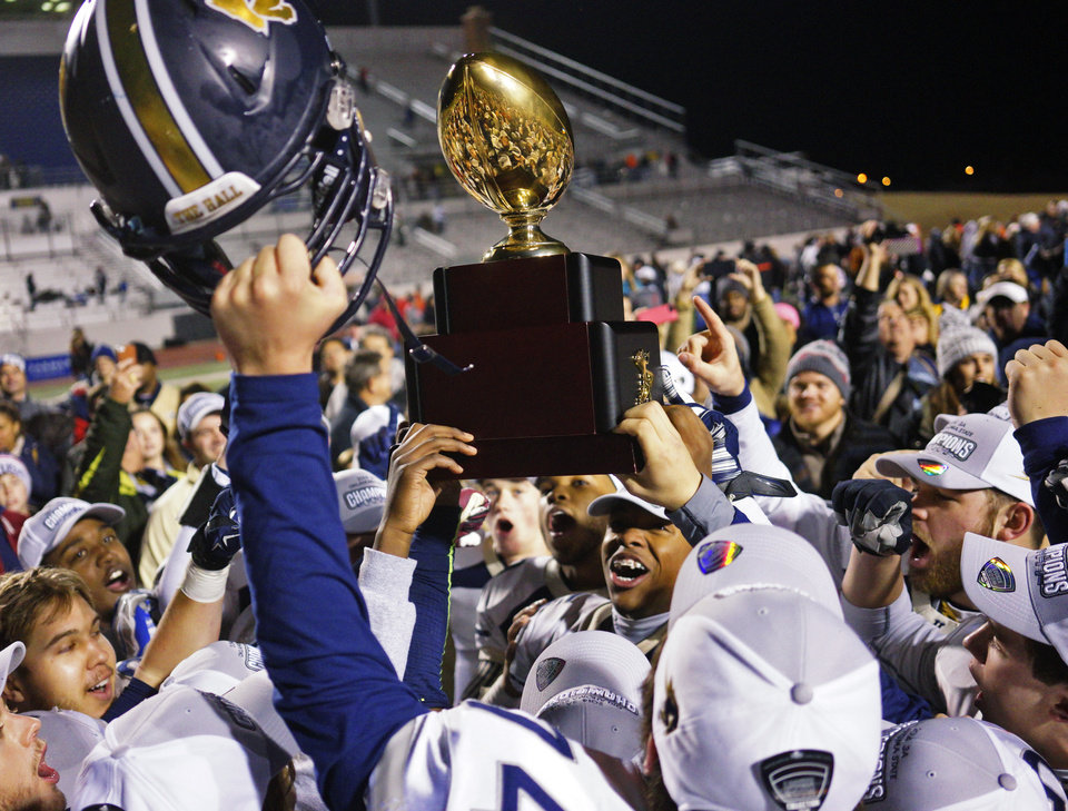 Photo -  Heritage Hall celebrates its 2014 state football championship. The Oklahoma Secondary Schools Activities Association board on Wednesday voted against a proposal that would have private schools compete separately from public schools in playoffs. [OKLAHOMAN ARCHIVES]