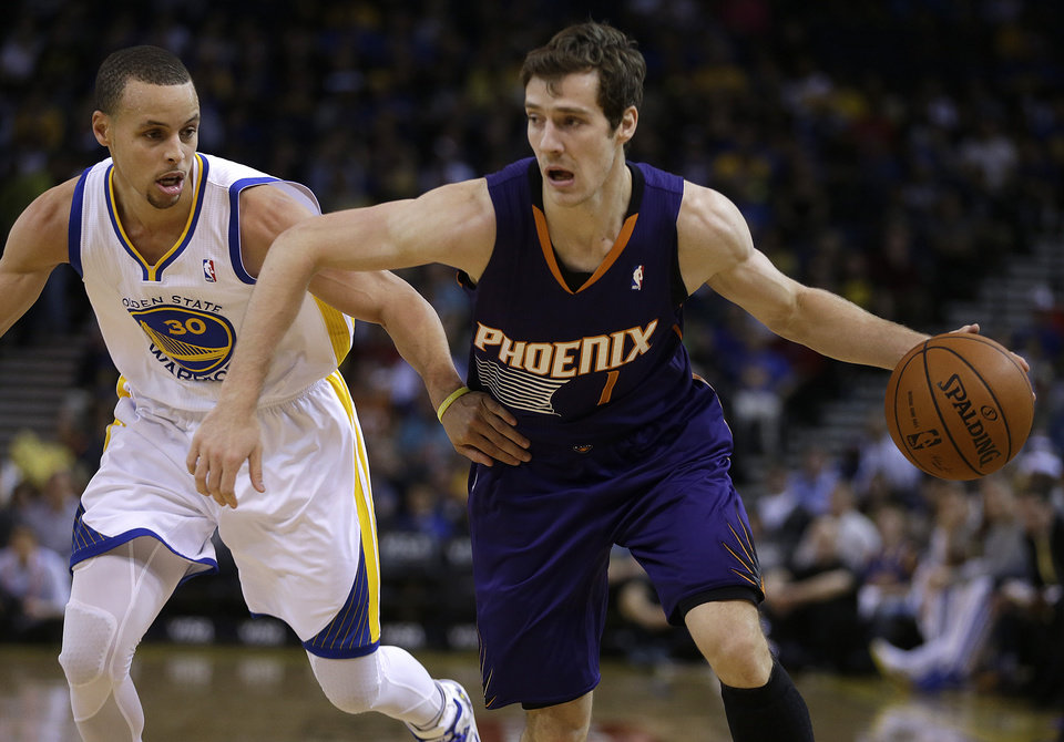 Photo - Phoenix Suns' Goran Dragic, right, drives the ball past Golden State Warriors' Stephen Curry (30) during the first half of an NBA basketball game Sunday, March 9, 2014, in Oakland, Calif. (AP Photo/Ben Margot)