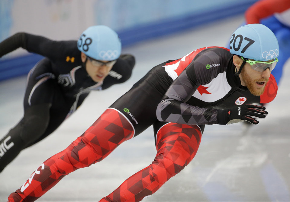 Photo - Olivier Jean of Canada, right, and J.R. Celski of the United States compete in a men's 500m short track speedskating heat at the Iceberg Skating Palace during the 2014 Winter Olympics, Tuesday, Feb. 18, 2014, in Sochi, Russia. (AP Photo/David J. Phillip )