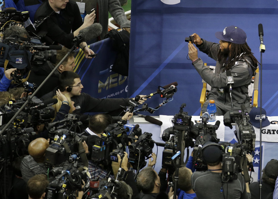 Photo - Seattle Seahawks' Richard Sherman takes some pictures during media day for the NFL Super Bowl XLVIII football game Tuesday, Jan. 28, 2014, in Newark, N.J. (AP Photo/Charlie Riedel)