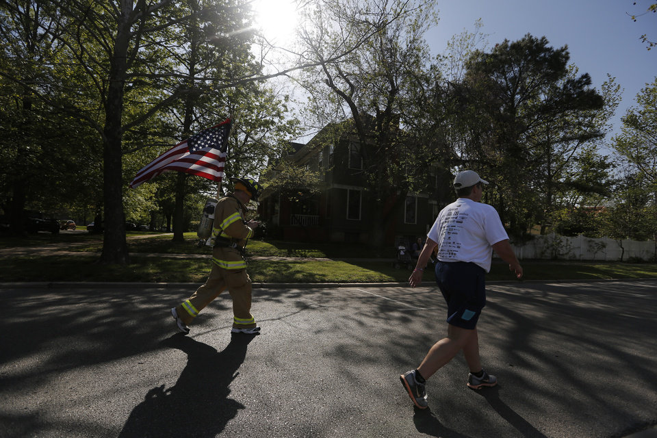 Photo - A firefighter carries an American flag during the Oklahoma City Memorial Marathon in Oklahoma City, Sunday, April 28, 2013.  Photo by Garett Fisbeck, For The Oklahoman