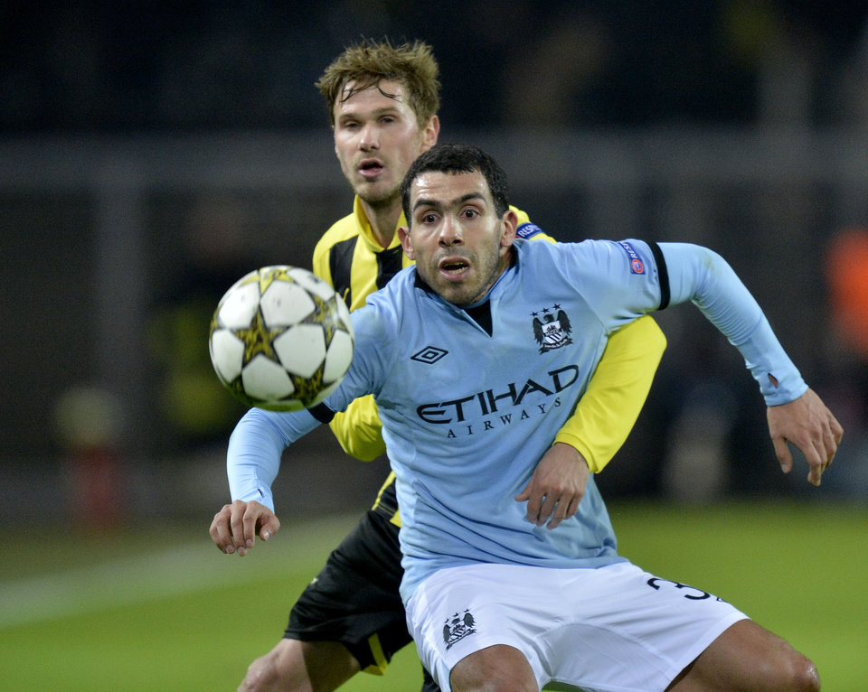 Carlos Tevez from Manchester City, right, and Dortmund\'s Oliver Kirch challenge for the ball during the Champions League Group D soccer match between Borussia Dortmund and Manchester City in Dortmund, Tuesday, Dec. 4, 2012. (AP Photo/Martin Meissner)