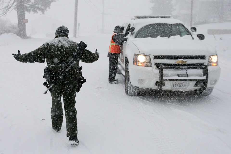 FILE - In this Feb. 8, 2013 file photo, San Bernardino Sheriff\'s Department offices stand guard at a check point during the search for fired Los Angeles Police Department officer Christopher Dorner in Big Bear Lake, Calif. (AP Photo/Chris Carlson, File)