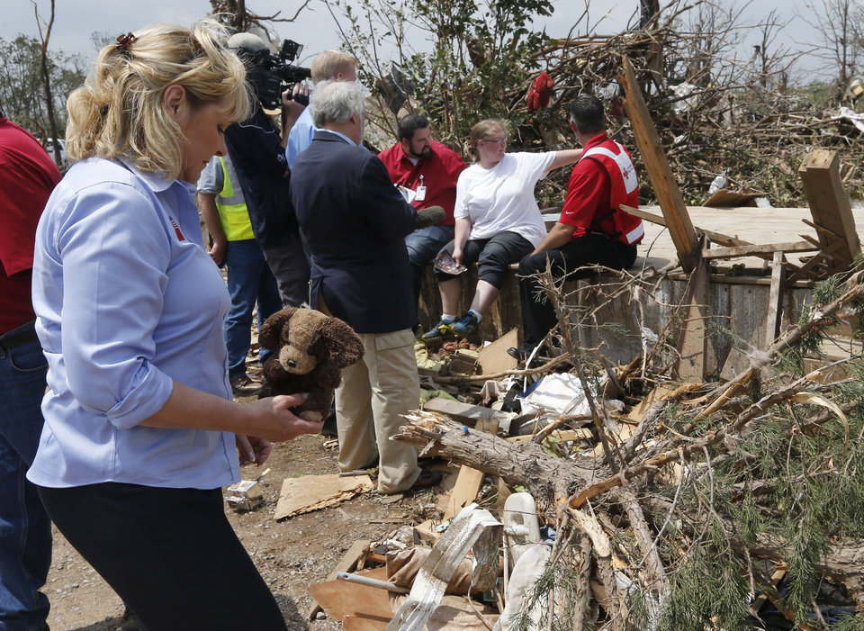 Photo - Oklahoma Gov. Mary Fallin, left, picks up a stuffed dog from the rubble of Kimberly Graham's home, at the Steelman Estates Mobile Home Park, which was hard hit in Sunday's tornado, near Shawnee, Okla., Monday, May 20, 2013. Graham is seated at rear in white talking with Red Cross workers. (AP Photo Sue Ogrocki)