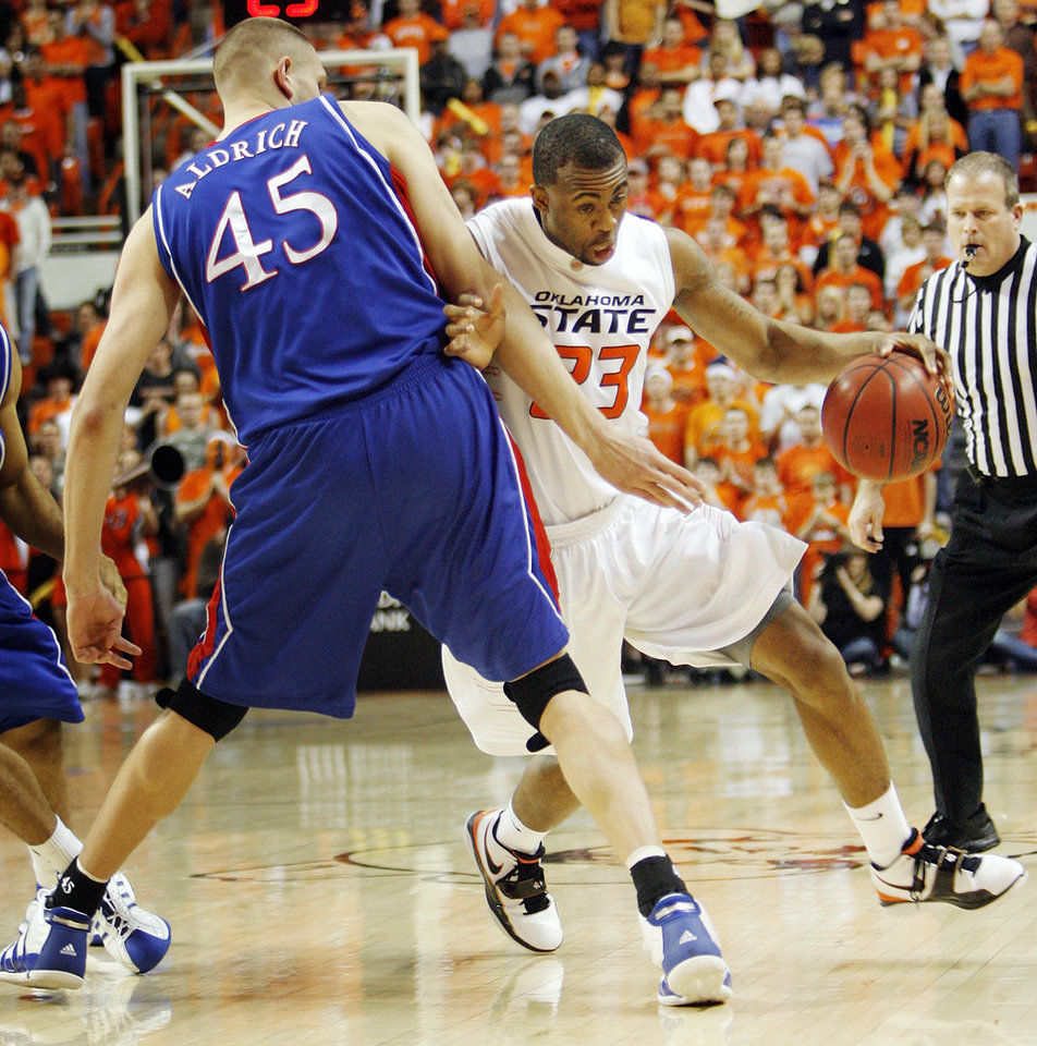 OSU's James Anderson (23) drives the ball around Cole Aldrich (45) of KU in the first half during the men's college basketball game between the University of Kansas (KU) and Oklahoma State University (OSU) at Gallagher-Iba Arena in Stillwater, Okla., Saturday, Feb. 27, 2010. Photo by Nate Billings, The Oklahoman