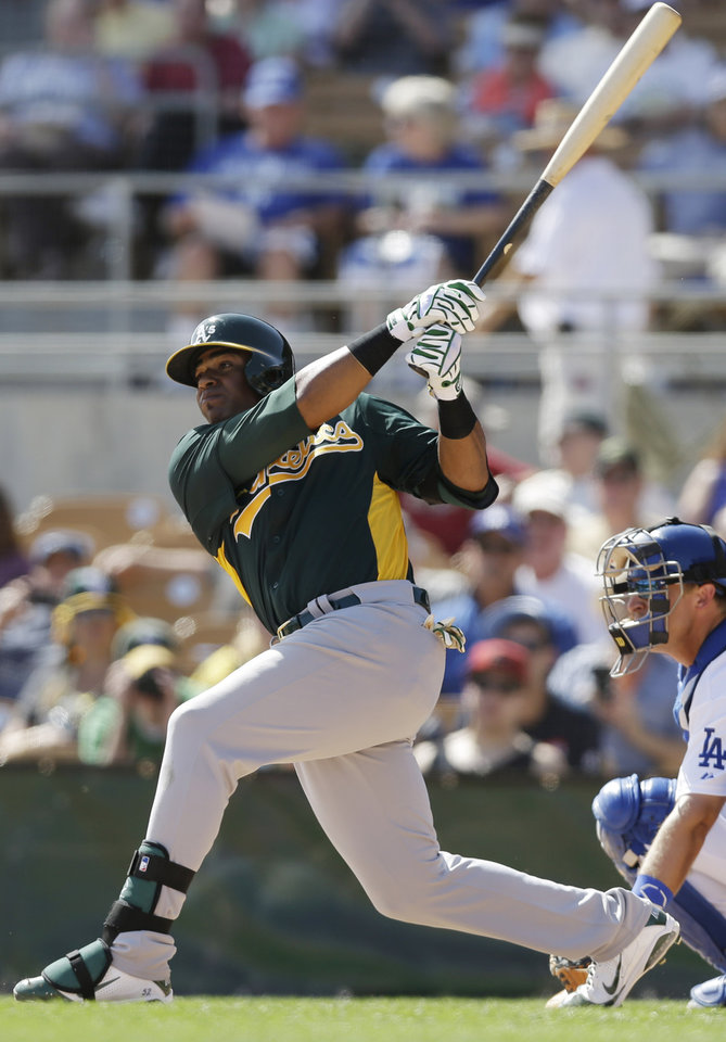 Photo - Oakland Athletics' Yoenis Cespedes watches his solo home run against the Los Angeles Dodgers during the fifth inning of a spring training baseball game Tuesday, March 19, 2013, in Glendale, Ariz. (AP Photo/Marcio Jose Sanchez)