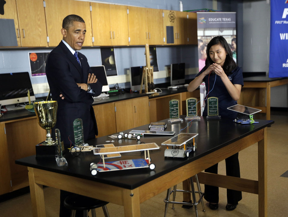 Photo - President Barack Obama, left, watches student Anh Ly, right, control a solar powered vehicle during a classroom visit to Manor New Technology High School, Thursday, May 9, 2013 in Manor, Texas. (AP Photo/Pablo Martinez Monsivais)