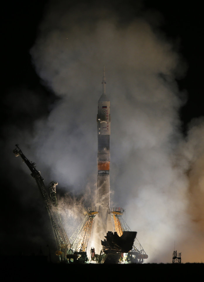 Photo - The Soyuz-FG rocket booster with Soyuz TMA-12M space ship carrying a new crew to the International Space Station (ISS) blasts off at the Russian leased Baikonur cosmodrome, Kazakhstan, Wednesday, March 26, 2014. The Russian rocket carries astronaut Steven Swanson, Russian cosmonauts Alexander Skvortsov and Oleg Artemyev. (AP Photo/Dmitry Lovetsky)