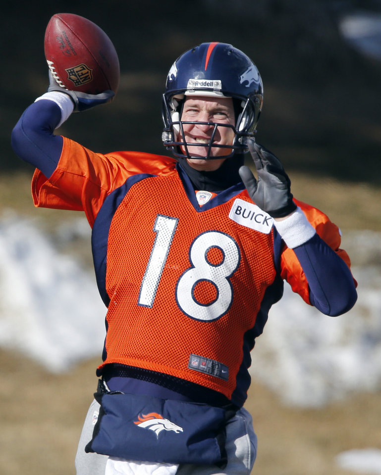 Photo - Denver Broncos quarterback Peyton Manning (18) tosses a football during practice for the football team's NFL playoff game against the San Diego Chargers at the Broncos training facility in Englewood, Colo., on Thursday, Jan. 9, 2014. (AP Photo/Ed Andrieski)