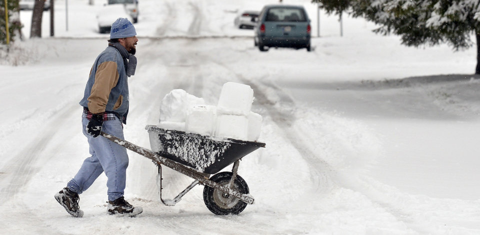 In this Dec. 26, 2012 photo, Concepcion Chavez, originally from Tampa, Fla., pushes a wheel barrel of snow blocks to his family's home to build an igloo in Terre Haute, Ind. (AP Photo/The Tribune-Star, Joseph C. Garza)