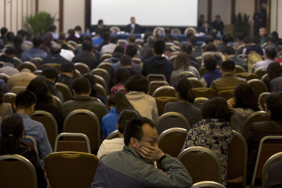 Photo - Relatives of Chinese passengers aboard the missing Malaysia Airlines flight MH370 attend a meeting with the Malaysian ambassador to China and a representative of Malaysia Airlines in Beijing, China, Monday, March 24, 2014. Rain was expected to hamper the hunt Monday for debris suspected of being from the missing Malaysia Airlines jet, as the United States prepared to move a specialized device that can locate black boxes into the south Indian Ocean region.  (AP Photo/Ng Han Guan)