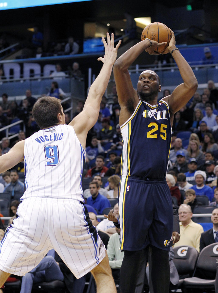 Utah Jazz center Al Jefferson (25) shoots over Orlando Magic center Nikola Vucevic (9) during the first half of an NBA basketball game, Sunday, Dec. 23, 2012, in Orlando, Fla. (AP Photo/Scott Iskowitz)