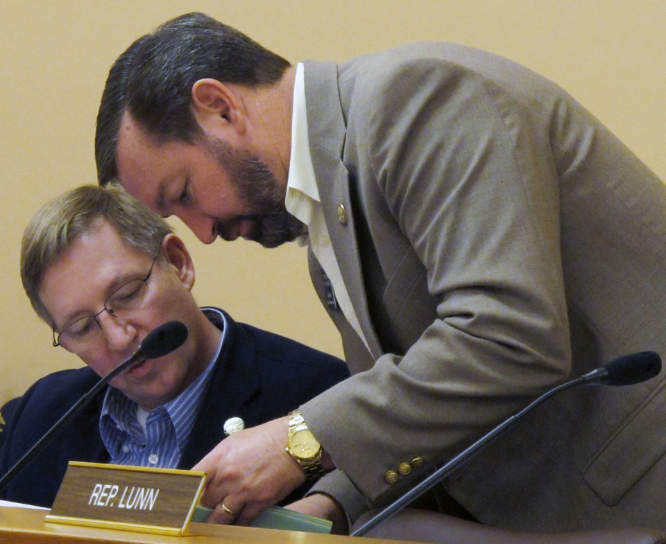 Photo - Kansas state Rep. Pete DeGraaf, left, a Mulvane Republican, consults with Rep. Virgil Peck, right, a Tyro Republican, during a break in a meeting of the House Appropriations Committee, Friday, Feb. 22, 2013, at the Statehouse in Topeka, Kan. The committee is considering a resolution against the expansion of Medicaid under the federal health care overhaul. (AP Photo/John Hanna)
