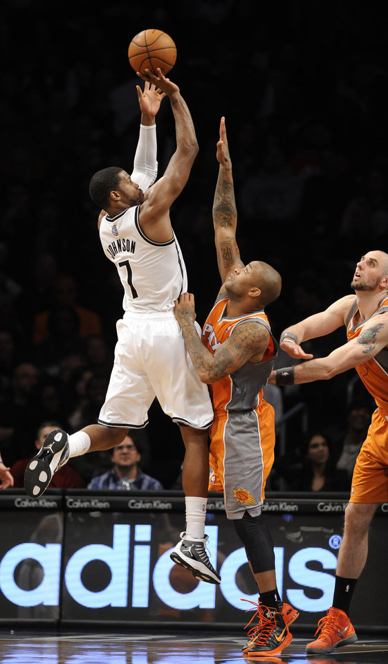 Brooklyn Nets' Joe Johnson (7) shoots over Phoenix Suns' P.J. Tucker (17) and  Marcin Gortat, right. in the second half of an NBA basketball game on Friday, Jan., 11, 2013 at Barclays Center in New York. The Nets won 99-79. (AP Photo/Kathy Kmonicek)
