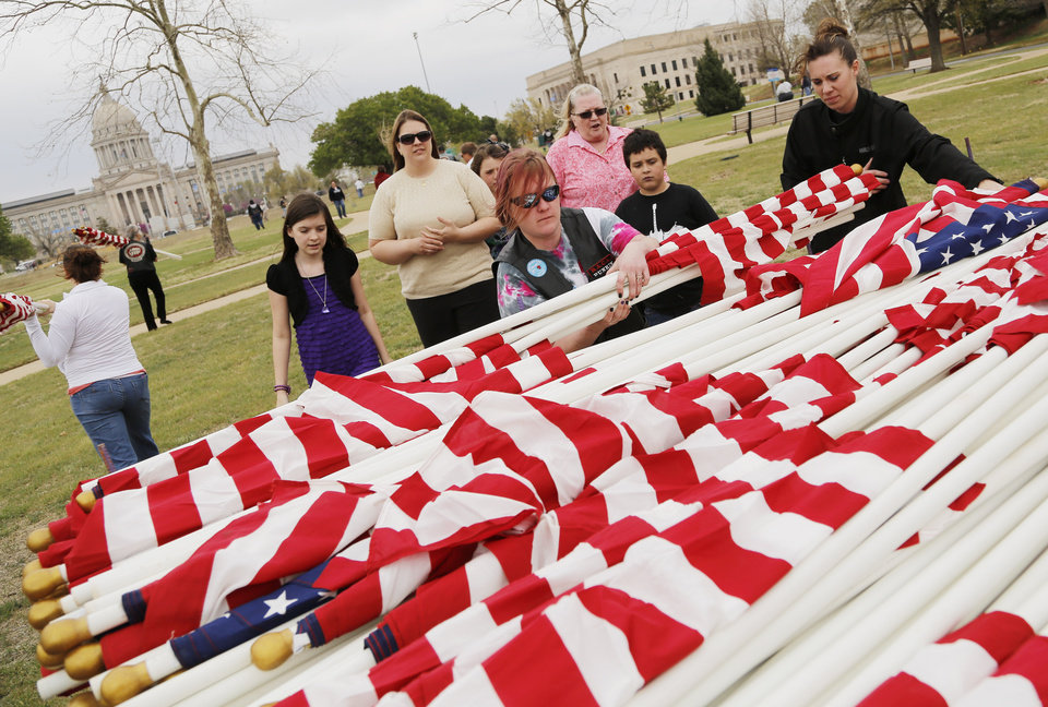 Volunteers grab armloads of American flags to be posted in honor of children who died in America in 2011 in the fields south of the state Capitol Sunday, April 7, 2013. Photo by Doug Hoke, The Oklahoman