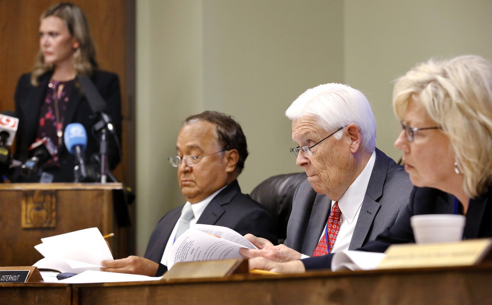 Photo - Seated, from left, are Dr. R. Murali Krishna, Ronald Osterhout and Becky Payton, board treasurer.  Standing at podium is Julie Ezell, general counsel for the health department.  The Oklahoma State Department of Health voted at their monthly meeting Tuesday morning, July 10, 2018, to ban sales of smokeable forms of medical marijuana and to require dispensaries to hire a pharmacist. The Board of Health voted on 75 pages of rules creating a rough framework for patients, physicians, caretakers and business owners interested in medical marijuana. The ban on sales of leaves and flowers for smoking and the requirement to hire a pharmacist weren't in the draft rules presented to the board, but were a priority of a coalition of medical groups. Julie Ezell, the Health Department's general counsel, presented the rules to a packed board room and to members of the public watching in an overflow room and online. She cautioned board members that the two new rules they added might not be allowed under the state question, inviting a court challenge. Photo by Jim Beckel, The Oklahoman