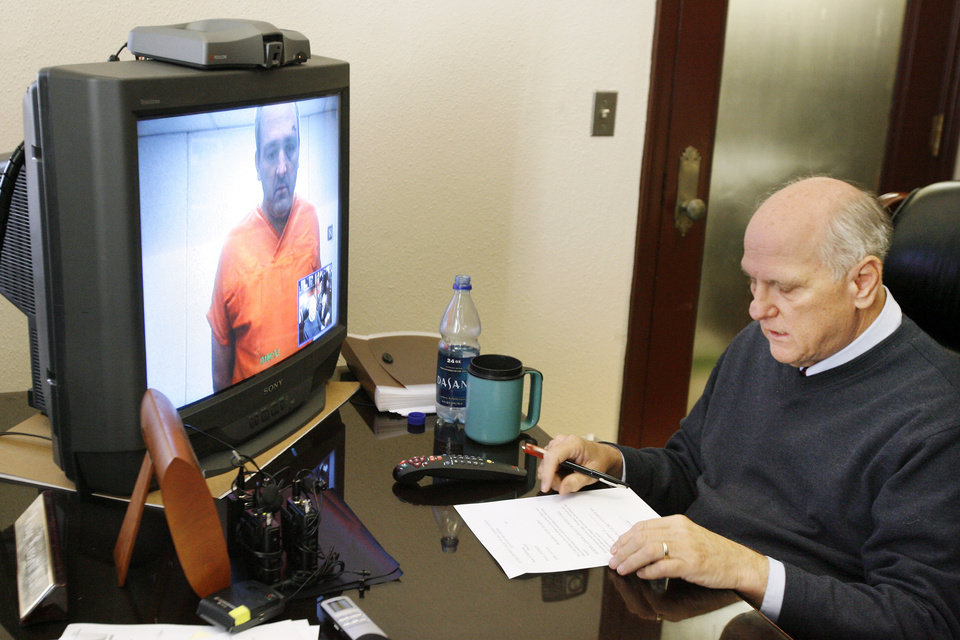 Photo - STEPHEN WOLF / MURDER / ASSAULT / ARREST / CHARGES / SON / CHILD: Stephen P. Wolf appears at left in a video monitor as Judge Russell Hall, right, conducts a video hearing in his chamber at the Oklahoma County Courthouse in Oklahoma City Wednesday, Nov. 18, 2009.  Photo by Paul B. Southerland, The Oklahoman ORG XMIT: KOD