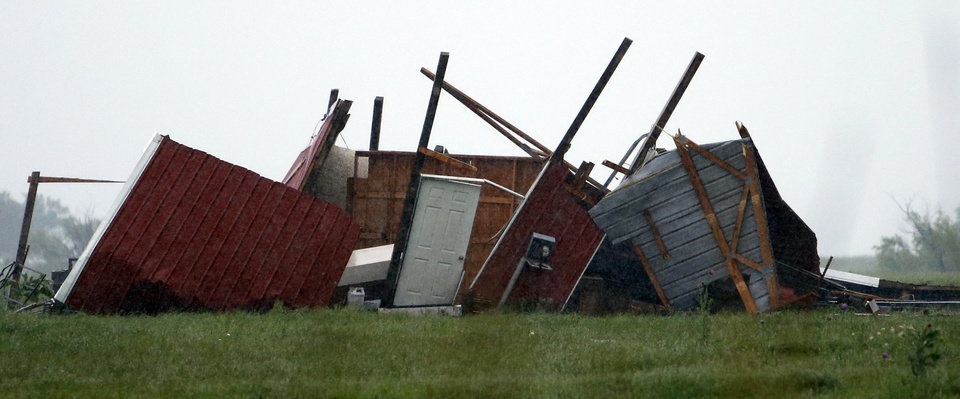 Photo - A barn on county road 1250 lies in the path of debris from a storm on Saturday, May 23, 2015 in Pocasset, Okla.  Photo by Steve Sisney The Oklahoman