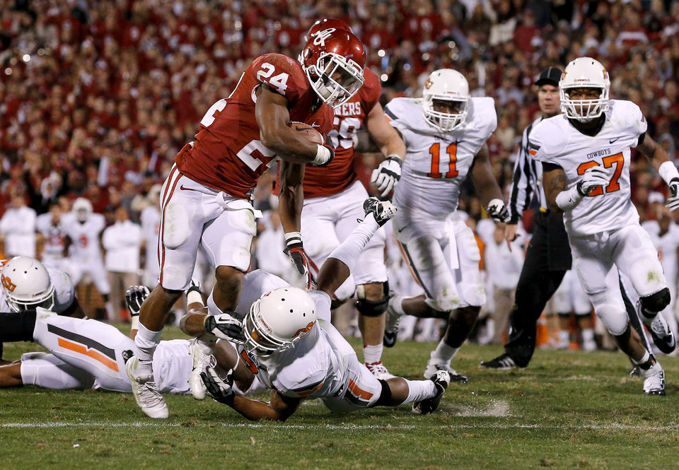 Oklahoma's Brennan Clay (24) runs past Oklahoma State's Shamiel Gary (7) to score the game-winning touchdown during the Bedlam college football game between the University of Oklahoma Sooners (OU) and the Oklahoma State University Cowboys (OSU) at Gaylord Family-Oklahoma Memorial Stadium in Norman, Okla., Saturday, Nov. 24, 2012. Oklahoma won 51-48. Photo by Bryan Terry, The Oklahoman