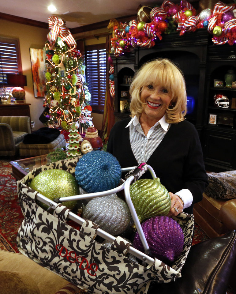 Photo - Debbie McCurdy arranges a basket of oversized ornaments in her home as she gets it ready for the Assistance League of Norman's Holiday Home Tour. PHOTO BY STEVE SISNEY, THE OKLAHOMAN  STEVE SISNEY