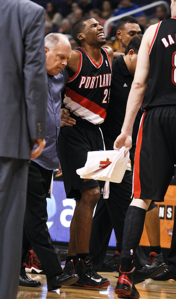 Portland Trail Blazers' Ronnie Price (24) grimaces as he is helped off the court after an injury in the second half of an NBA preseason basketball game against the Phoenix Suns Friday, Oct. 12, 2012, in Phoenix. The Suns defeated the Trail Blazers 104-93.(AP Photo/Ross D. Franklin)
