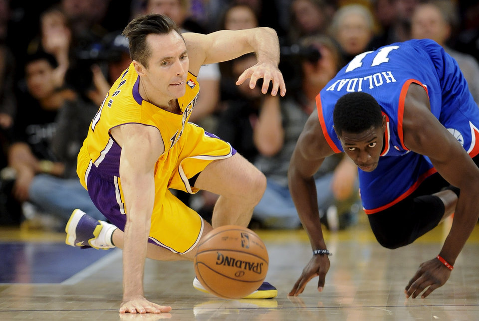 Los Angeles Lakers guard Steve Nash, left, and Philadelphia 76ers guard Jrue Holiday, right, fight for a loose ball in the first half of an NBA basketball game, Tuesday, Jan. 1, 2013, in Los Angeles. (AP Photo/Gus Ruelas)