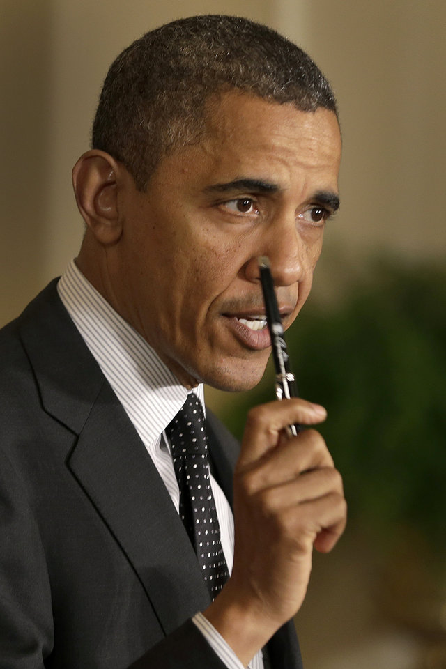 President Barack Obama holds up a pen as he speaks about the economy and the deficit, Friday, Nov. 9, 2012, in the East Room of the White House in Washington. (AP Photo/Jacquelyn Martin)
