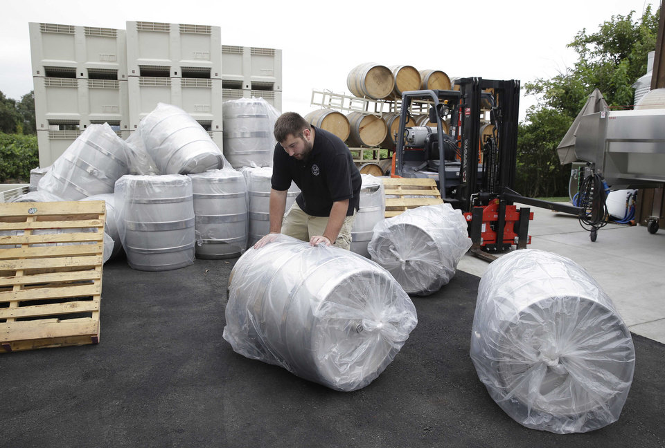 Photo - Tyler Dahl looks over stainless steel wine barrels that fell following an earthquake at Dahl Vineyards Sunday, Aug. 24, 2014, in Yountville, Calif. A large earthquake caused significant damage and left at least three critically injured in California's northern Bay Area early Sunday, igniting fires, sending at least 87 people to a hospital, knocking out power to tens of thousands and sending residents running out of their homes in the darkness.  (AP Photo/Eric Risberg)