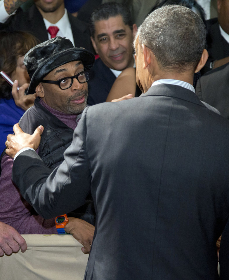 Photo - President Barack Obama greets Spike Lee, film director, producer, writer, and actor, left, at Rev. Al Sharpton's National Action Network conference, Friday, April 11, 2014, in New York. (AP Photo/Carolyn Kaster)