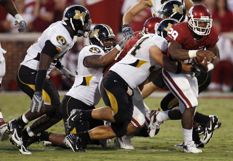 Photo - Oklahoma's Chris Brown (29) drags a trail of Missouri defenders behind him on a run during the first half of the college football game between the University of Oklahoma Sooners (OU) and the University of Missouri Tigers (MU) at the Gaylord Family Oklahoma Memorial Stadium on Saturday, Oct. 13, 2007, in Norman, Okla.By STEVE SISNEY, The Oklahoman
