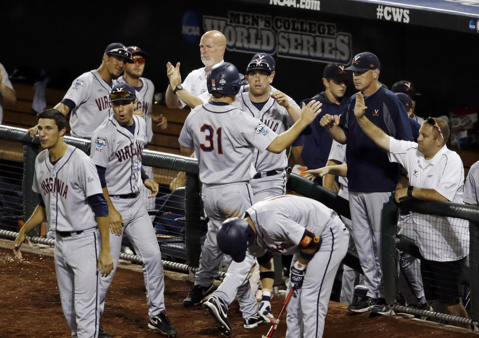 Photo - Virginia's Joe McCarthy (31) celebrates with teammates after scoring in the seventh inning of Game 2 of the best-of-three NCAA baseball College World Series finals against Vanderbilt in Omaha, Neb., Tuesday, June 24, 2014. (AP Photo/Nati Harnik)