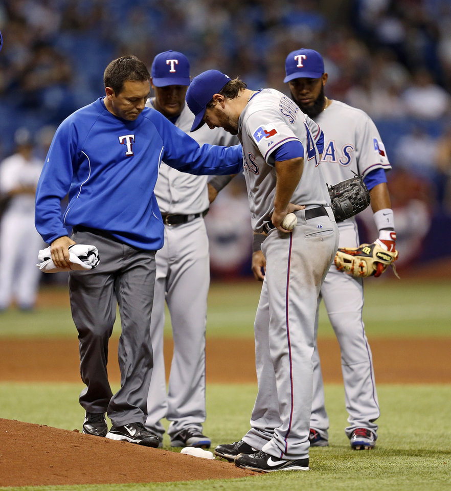 Photo - Texas Rangers starting pitcher Joe Saunders is attended to by assistant trainer Matthew Lucero after Saunders was hit on the leg by a ball struck by Tampa Bay Rays' Evan Longoria during the fourth inning of a baseball game Friday, April 4, 2014, in St. Petersburg, Fla. Saunders left the game. (AP Photo/Mike Carlson)