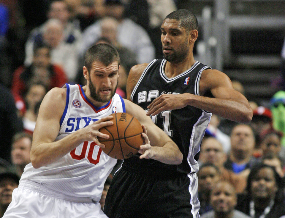 San Antonio Spurs' Tim Duncan defends as Philadelphia 76ers' Spencer Hawes (00) looks to pass in the first half of an NBA basketball game Monday Jan. 21, 2013, in Philadelphia. (AP Photo H. Rumph Jr)