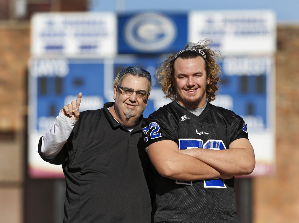Photo - Guthrie High School defensive lineman Trevor Blassingame and his father, Doc, pose at Guthrie's Jelsma Stadium for Friday Night Lights feature.  Doc wears his dyed blue hair cut in a Mohawk after promising Trevor during his freshman year he would sport one when he became a starter on the varsity squad.  Photo taken Wednesday, Nov. 27, 2013.  Photo by Jim Beckel, The Oklahoman