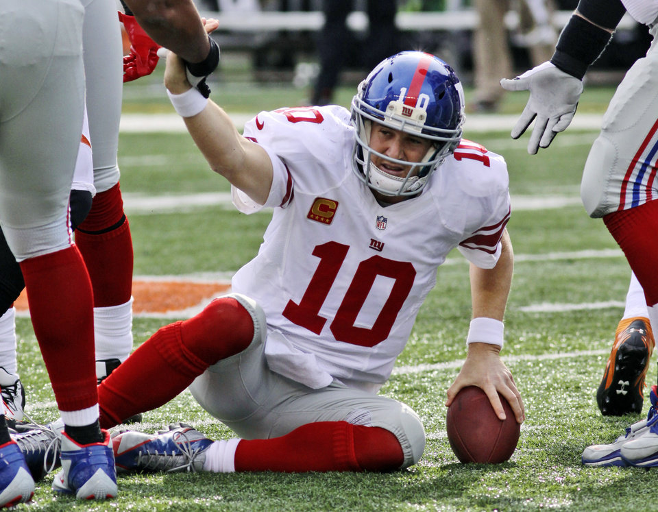 Photo -   New York Giants quarterback Eli Manning is helped up after being sacked in the second half of an NFL football game against the Cincinnati Bengals, Sunday, Nov. 11, 2012, in Cincinnati. (AP Photo/Tom Uhlman)