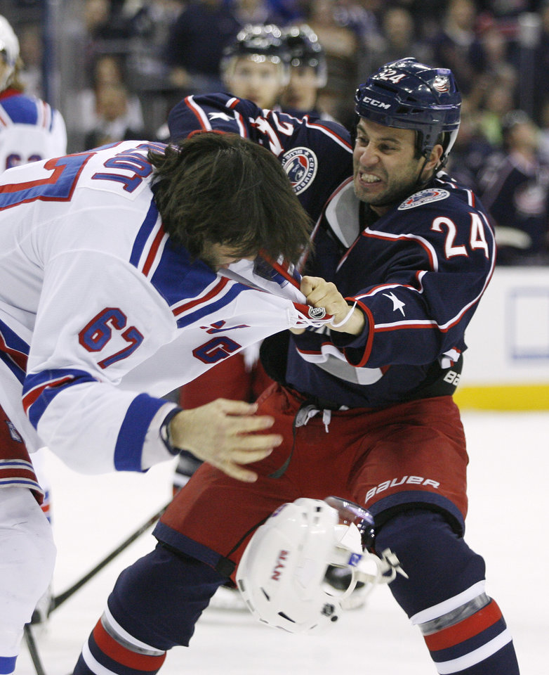 Photo - Columbus Blue Jackets' Derek MacKenzie (24) fights New York Rangers' Benoit Pouliot (67) during the first period of an NHL hockey game, Friday, March 21, 2014, in Columbus, Ohio. (AP Photo/Mike Munden)