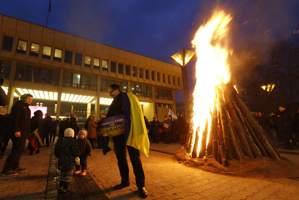 Photo - Lithuanians burn a  bonfire during the protest against the violence in Ukraine in front of the Lithuania  Parliament building  in Vilnius, Lithuania, Wednesday, Feb. 19, 2014. The deadly clashes in Ukraine's capital have drawn sharp reactions from Washington, sparked a rapidly growing push for European Union sanctions and led to a Kremlin statement blaming Europe and the West. (AP Photo/Mindaugas Kulbis)