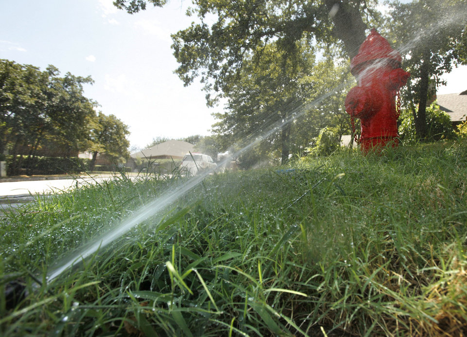 A sprinkler system runs Friday at an Edmond home. Photo By Paul Hellstern, The Oklahoman
