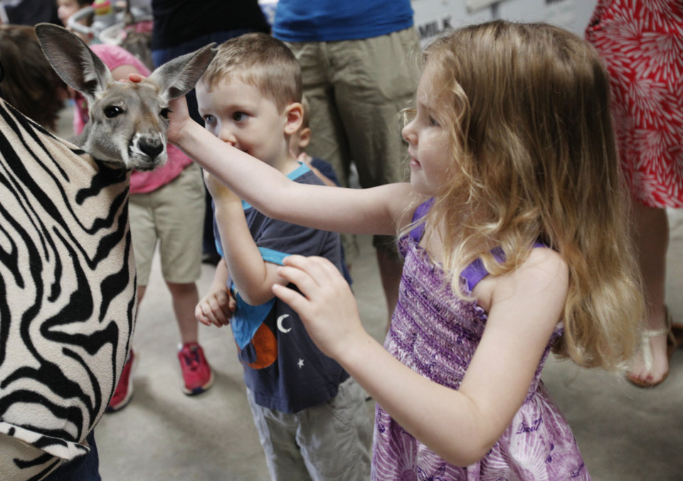 Photo - Four-year-old Adelynne Witherspoon pets Boomer, a young red kangaroo, at the farmer's market on the campus of OSU-OKC on June 5, 2013. Photo by KT KING, The Oklahoman