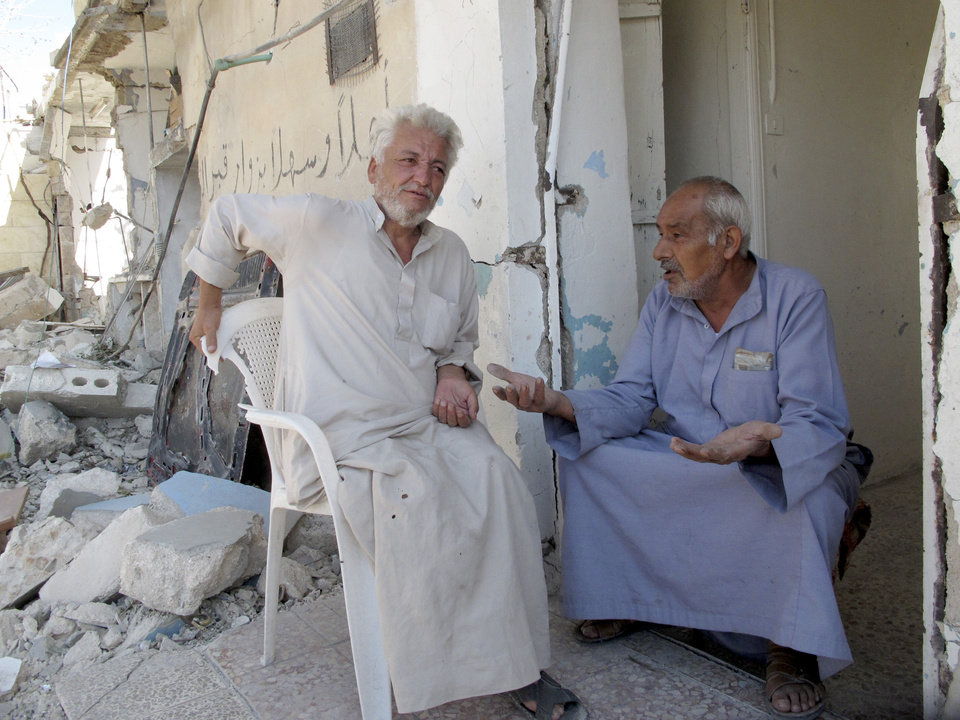 Photo -   Syrians Bassem Kharfani, left, and Mahmoud Jikar sit at the door of Jikar's house, one of more than a dozen homes destroyed in a Syrian government bombing last week that killed more than 40 people, in Azaz, Syria, on Monday, Aug. 20, 2012. (AP Photo/Ben Hubbard)