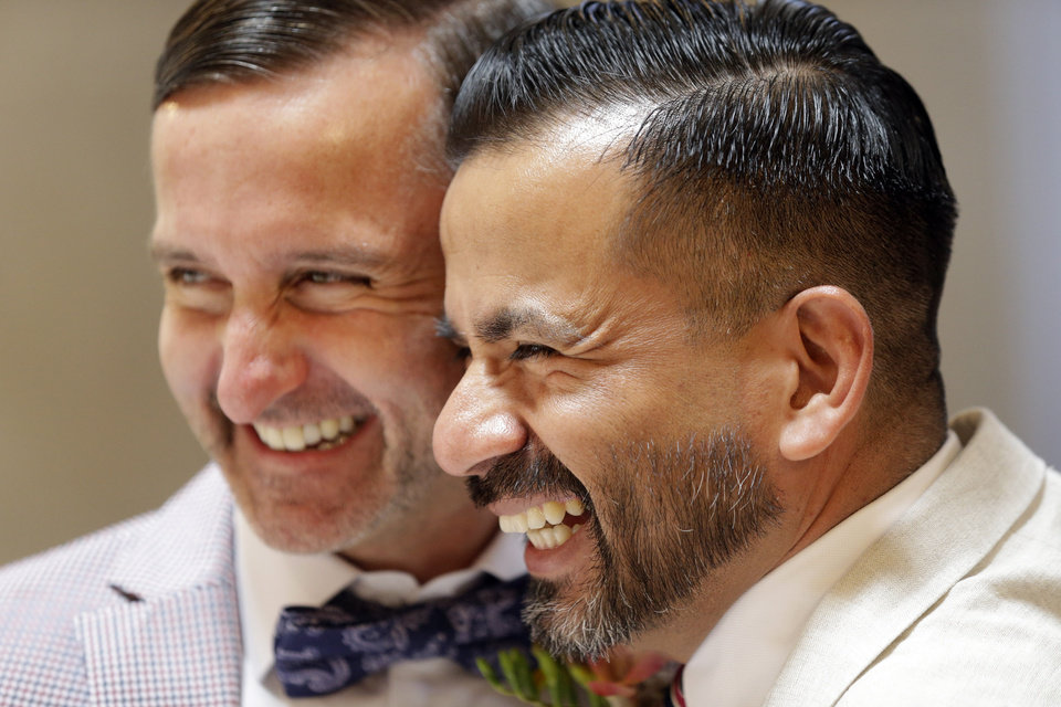 Photo - Peter Madril, left, and Monte Young embrace after getting married at City Hall in San Francisco, Saturday, June 29, 2013. Dozens of gay couples waited excitedly Saturday outside of San Francisco's City Hall as clerks resumed issuing same-sex marriage licenses, one day after a federal appeals court cleared the way for the state of California to immediately lift a 4 ½ year freeze. Big crowds were expected from across the state as long lines had already stretched down the lobby shortly after 9 a.m. City officials decided to hold weekend hours and let couples tie the knot as San Francisco is also celebrating its annual Pride weekend expected to draw as many as 1 million people. (AP Photo/Marcio Jose Sanchez)