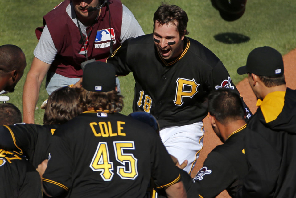 Pittsburgh Pirates' Neil Walker (18) is greeted by teammates after hitting a walk-off solo-home run off Chicago Cubs relief pitcher Carlos Villanueva during the tenth inning of a baseball game in Pittsburgh Monday, March 31, 2014. The Pirates won 1-0 in ten innings.(AP Photo/Gene J. Puskar)