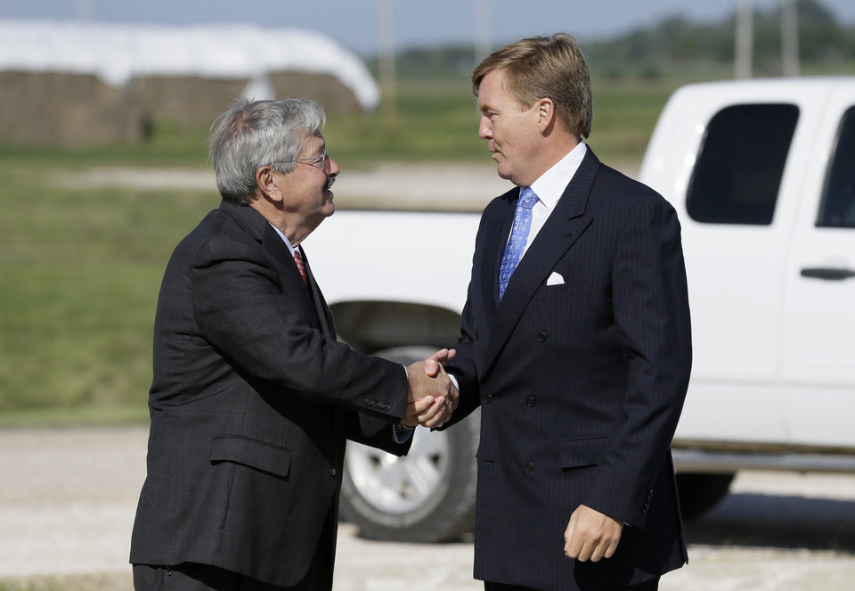 Photo - King Willem-Alexander of the Netherlands is greeted by Iowa Gov. Terry Branstad, left, while arriving at the opening of one of the nation's first commercial size cellulosic ethanol plants, Wednesday, Sept. 3, 2014, in Emmetsburg, Iowa. Project Liberty is a $250 million plant that will make 25 million gallons of ethanol a year from corn cobs, stalks, leaves and other plant residue. The project is a joint venture of Sioux Falls, South Dakota-based ethanol-maker POET and Royal DSM, a Netherlands biotechnology company. (AP Photo/Charlie Neibergall)