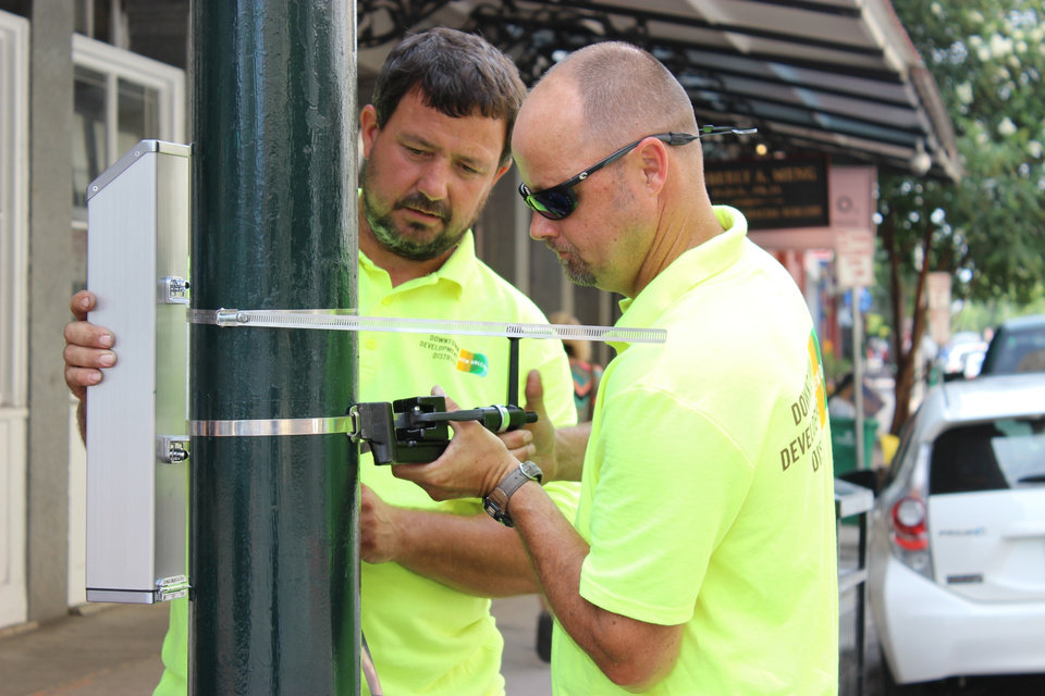 Photo - Dale Alvin, right, tightens the strap holding a cigarette butt recycling container to a lamp post in New Orleans' Warehouse District on Monday, July 21, 2014, while Jerry Howell holds it upright. The city's Downtown Development District plans to install about 50 of the receptacles around New Orleans in what manufacturer TerraCycle Inc. says is the first citywide cigarette butt recycling program in the United States. TerraCycle will pay $4 per pound for the cigarette waste, which it turns into shipping pallets. (AP Photo/Janet McConnaughey)