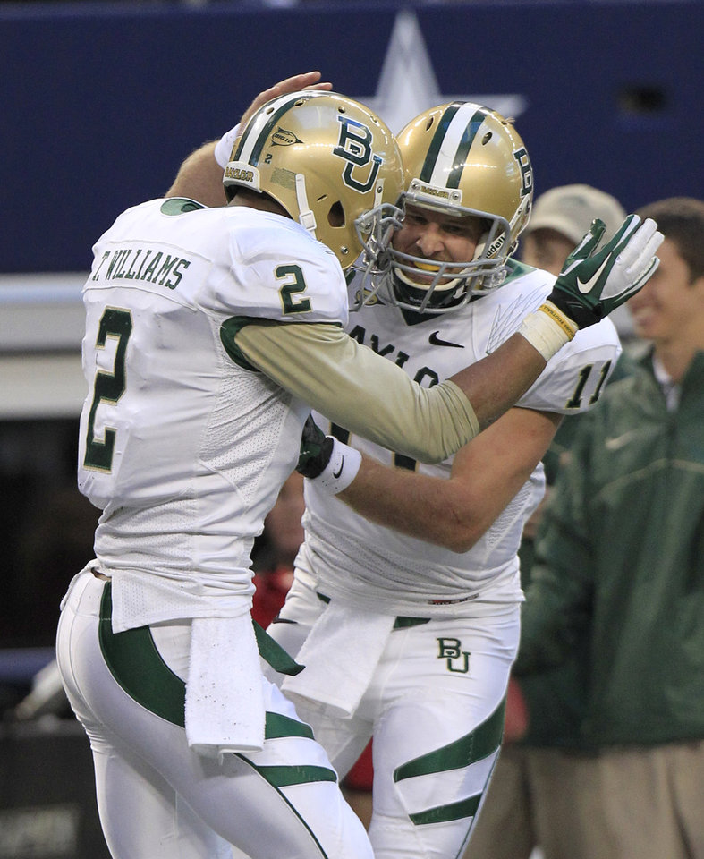 Baylor quarterback Nick Florence (11) celebrates a touchdown with wide receiver Terrance Williams (2) during the second half of the NCAA college football game Saturday, Nov. 24, 2012, in Arlington, Texas. Baylor won 52-45 in overtime. (AP Photo/LM Otero)