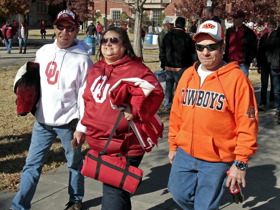 All in the family--John Johnson and his sister-in-law Tonja (left) are OU fans but Tonja's husband Vic roots for the opporition as they head toward the Bedlam college football game between the University of Oklahoma Sooners (OU) and the Oklahoma State University Cowboys (OSU) at Gaylord Family-Oklahoma Memorial Stadium in Norman, Okla., Saturday, Nov. 24, 2012. Photo by Steve Sisney, The Oklahoman