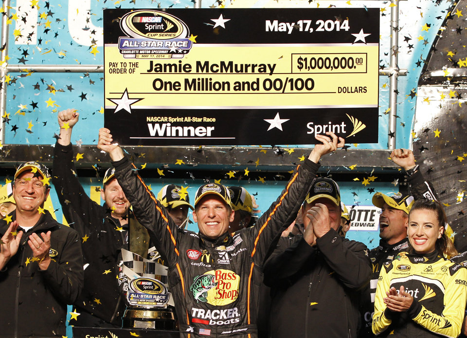 Photo - Jamie McMurray raises the mock check in Victory Lane after winning the NASCAR Sprint All-Star auto race at Charlotte Motor Speedway in Concord, N.C., Saturday, May 17, 2014. (AP Photo/Terry Renna)