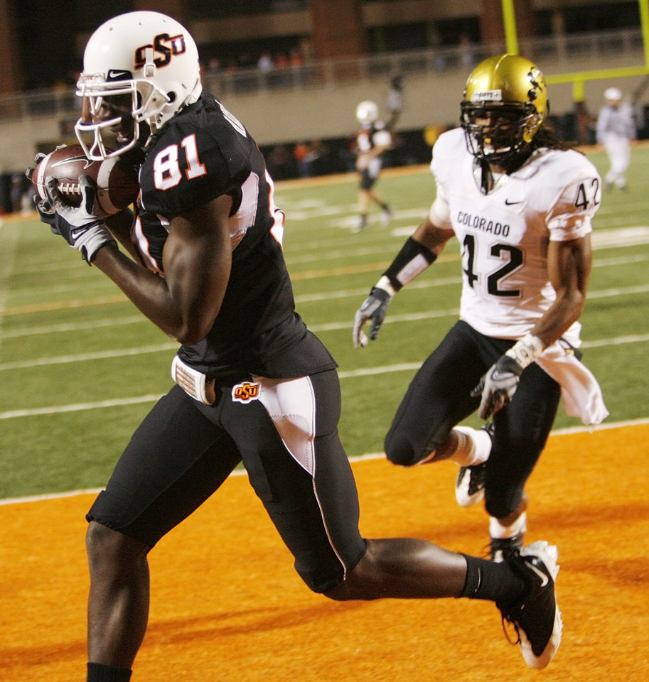 Photo - OSU's Justin Blackmon (81) catches a touchdown pass from Brandon Weeden (not pictured) in front of Colorado's Benjamin Burney (42) in the fourth quarter during the college football game between Oklahoma State University (OSU) and the University of Colorado (CU) at Boone Pickens Stadium in Stillwater, Okla., Thursday, Nov. 19, 2009. OSU won, 31-28. Photo by Nate Billings, The Oklahoman