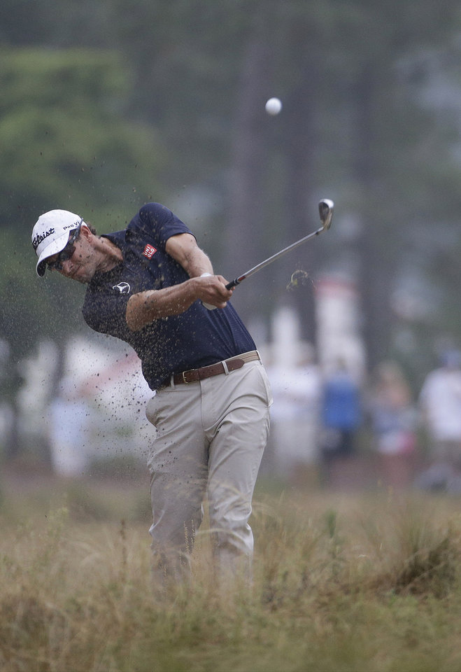 Photo - Adam Scott, of Australia, hits from the natural area on the 12th hole during the second round of the U.S. Open golf tournament in Pinehurst, N.C., Friday, June 13, 2014. (AP Photo/David Goldman)