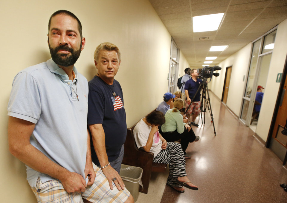 Photo - Kenny Wright, left, and Bo Bass wait to apply for their marriage license at the Oklahoma County Courthouse in Oklahoma City, Monday October, 6 2014.They were the 3rd same sex couple to receive a marriage license in Oklahoma County. Photo By Steve Gooch, The Oklahoman